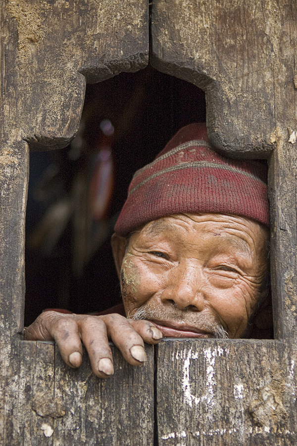 Retired tamang sherpa leaning on his home's window ledge in Timure village, Langtang region