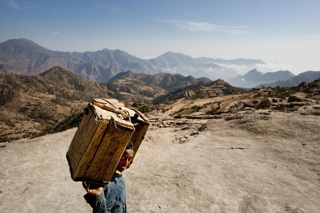 Un portatore comincia la discesa di 1200 metri che dal villaggio di Geblen porta a Gunda Gunde, ancora ammantato dalla nebbia del primo mattino