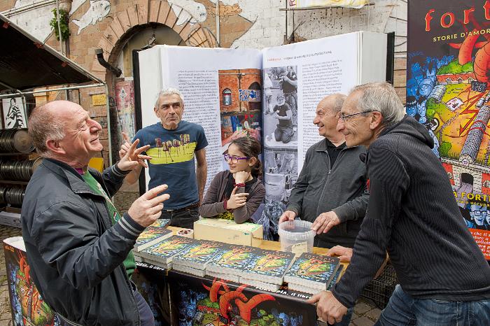 """""""Angelo delle api"""" e altri storici occupanti davanti al banchetto con le prime copie di Fortopìa"""