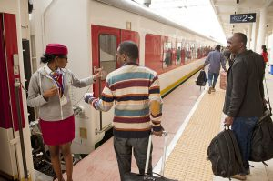Ethiopian railway staff member helps passengers get their seats on the Addis-Gibuti new train