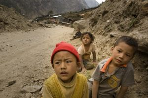 Tamang children playing on the new highway dusty ground at Timure village